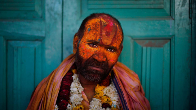 A Sadhu or Hindu holy man leans against a closed door at the Nandagram Temple famous for Lord Krishna during Lathmar Holi festival in Nandgaon.