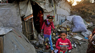 Murshida, 12, and her seven-year-old brother Shahidul step out of their rented shanty as they leave for the train station, on the outskirts of New Delhi, India.