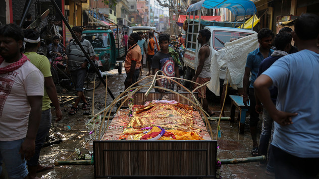 People walk past the body of a Hindu woman placed on a bed in the middle of a street, waiting to be cremated at the submerged Harishchandra Ghat on the banks of the river Ganges in Varanasi, one of the Hinduism's holiest cities, India, Saturday, Sept. 21, 2019. As the mighty Ganges River overflows following heavy monsoon rains, large parts of the Hindu holy town of Varanasi were submerged by floodwaters, forcing thousands of cremations to happen on rooftops and narrow alleyways. For millions of Hindus, Varanasi is a place of pilgrimage and anyone who dies in the city or is cremated on its ghats is believed to attain salvation and freed from the cycle of birth and death.