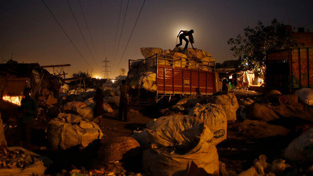 a worker loads segregated trash for recycling on a truck on the outskirts of New Delhi, India. Rag picking is effectively the primary recycling system in India. While the rag pickers offer invaluable services to the city, they have few rights and are exposed to deadly poisons everyday.