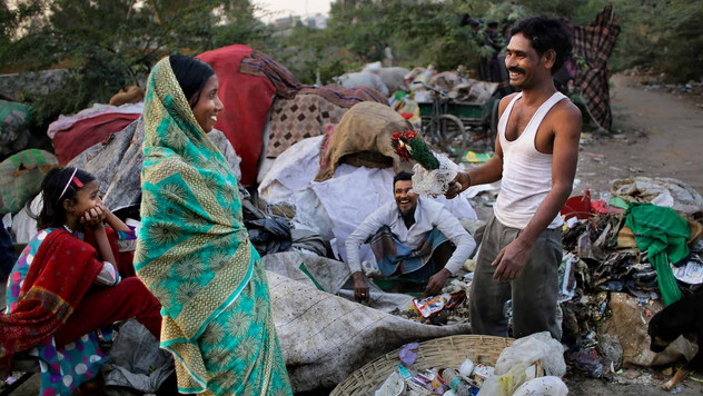 A neighbor teasingly gives a withered bouquet of flowers, found in a bag of trash, to Marjina outside their rented shanty on the outskirts of New Delhi, India.