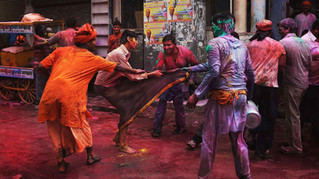 Indians pull the dhoti of a passerby as they tease him during holi celebrations outside Banke Bihari temple in Vrindavan, India.