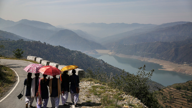 School girls walk along a road overlooking Tehri Dam in the northern Indian state of Uttarakhand, Monday, May 13, 2019. The Tehri Dam built on the Bhagirathi river is India's highest dam and supplies power and water to numerous Indian towns and cities. The Bhagirathi river is one of the two sources that form the River Ganges, the other being the river Alaknanda.