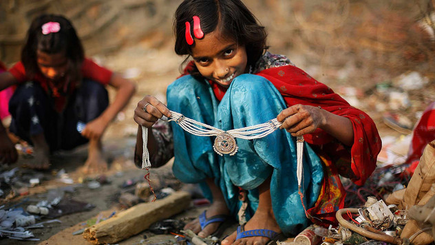 Murshida, 12, shows a necklace she found while segregating trash outside her rented shanty.