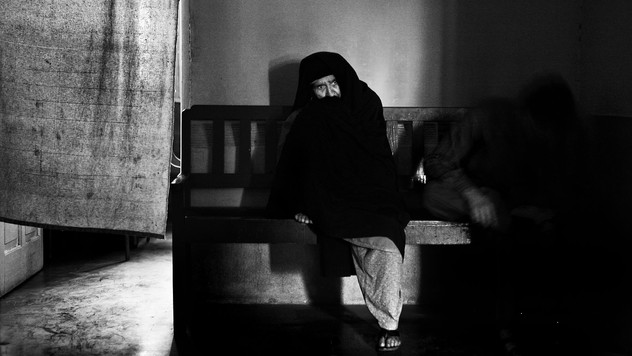 Mughli sits on a wooden bench outside a court room as she waits for her turn during the hearing into the case of her disappeared son in Srinagar, the summer capital of Indian-administered Kashmir, Sept. 13, 2007.