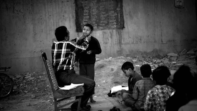 Founder of a free school for slum children, Rajesh Kumar Sharma, adjusts the collar of Somnath, an underprivileged Indian slum child, at a free school run under a metro bridge in New Delhi, India, Wednesday, Nov. 7, 2012.