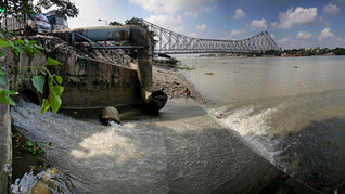 A man is seen defecating in open near the mouth of a sewage flowing directly in the river Hooghly, a distributary of the river Ganges and known as Ganga by locals, in the backdrop of the landmark Howrah Bridge in Kolkata, in the eastern Indian state of West Bengal, Friday, October 11, 2019. Once the capital of the British raj, today the seething metropolis is home to nearly 15 million people.