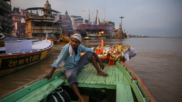 A worker who helps cremate bodies sits by the body of an elderly man, wrapped and weighed down by a large rock, before throwing the body into the river Ganges as per his final wish, on the banks of river Ganges in Varanasi, India, Friday, Oct. 18, 2019. For millions of Hindus, Varanasi is a place of pilgrimage and anyone who dies in the city or is cremated on its ghats is believed to attain salvation and freed from the cycle of birth and death. Tens of thousands of corpses are cremated in the city each year, leaving half-burnt flesh, dead bodies and ash floating in the Ganges.
