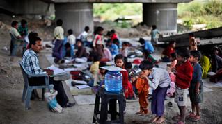Underprivileged children line-up to drink clean bottled water donated by philanthropists at free school run under a metro bridge in New Delhi, India, Mar. 19, 2013.
