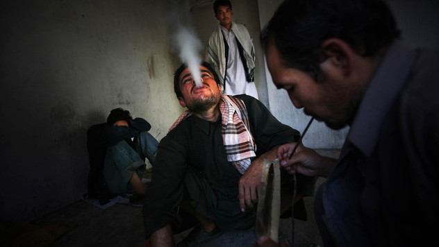 Afghan opium addicts squat on the floor as they smoke opium inside the bombed-out ruins of the former Russian Cultural Center, in Kabul, 2009.