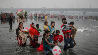 An Indian Hindu family walks on the shallow banks of the Yamuna river, covered with chemical foam caused by industrial and domestic pollution, during Chhath Puja festival in New Delhi, India, Saturday, Nov. 2, 2019. Despite the river being accorded the status of a living human entity by an Indian court, untreated sewage and industrial pollutants have turned it into one of the most polluted rivers in the world. The river Yamuna is one of the major tributaries of the Ganges.