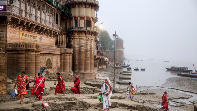 Hindu women walk on silt, deposited by monsoon floods, along the banks of the river Ganges to perform daily morning rituals in Varanasi, one of the Hinduism's holiest cities, in the northern Indian state of Uttar Pradesh, Friday, Oct. 18, 2019. For millions of Hindus, Varanasi is a place of pilgrimage and anyone who dies in the city or is cremated on its ghats is believed to attain salvation and freed from the cycle of birth and death.