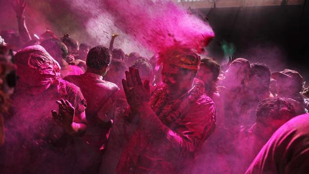 Colored powder falls on a Hindu devotee as he prays at the Banke Bihari temple during Holi festival in Vrindavan, India.