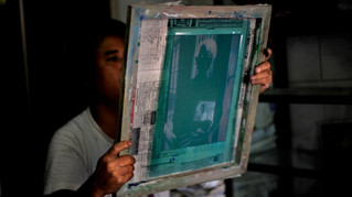 A printing factory worker looks at the screen stencil of the photograph of Myanmar's pro-democracy icon Aung San Suu Kyi before screen-printing it on T-shirts in Yangon, Myanmar.