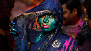 An Indian Hindu woman, drenched in colored water, looks on at the Nandagram Temple famous for Lord Krishna during Lathmar Holi festival in Nandgaon.