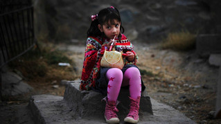 A young Afghan girl applies lipstick as she sits on a grave stone in the old part of Kabul, Afghanistan, 2010.