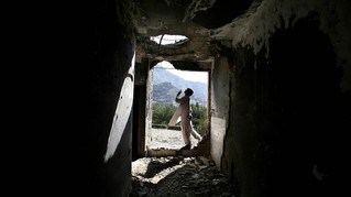 An Afghan opium addict bargains for a pack of opium from a supplier, not seen, on the terrace of the bombed-out ruins of the former Russian Cultural Center, in Kabul.