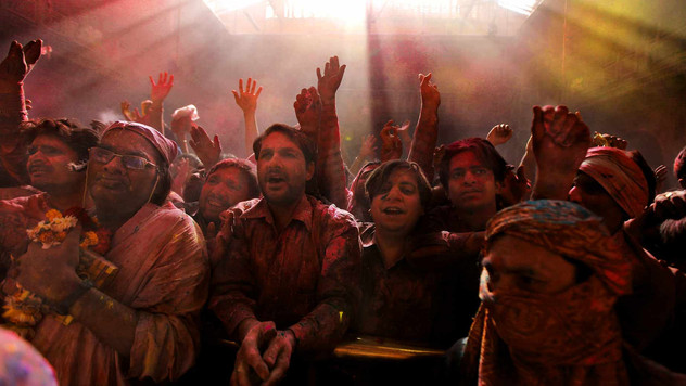 Hindu devotees covered with colored powder shout religious slogans inside Banke Bihari temple during Holi festival celebrations in Vrindavan, India.
