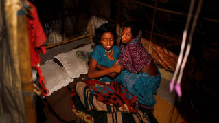 Marjina tends to her sick daughter Murshida, 12, as her son Shahid-ul, 7, lies beside, inside their rented shanty on the outskirts of New Delhi, India, Oct. 2014.