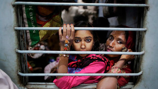 Murshida, 12, sits on the lap of her mother Marjina as the train leaves for their village in West Bengal, at a railway station in New Delhi, India.
