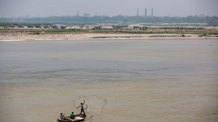 A fisherman casts his net into the river Ganges as trucks engaged in sand mining are seen in the distance in Kanpur, an industrial city known for its leather tanneries, in the northern Indian state of Uttar Pradesh, Wednesday, June 24, 2020. Kanpur city produces an estimated 450 million liters of municipal sewage and industrial effluent daily, much of which flowed directly into the Ganges until recently. Today that number is lower, though it's not clear by how much, after a Ganges cleanup project closed some drains and diverted industrial pollution to treatment plants.