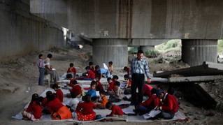 Underprivileged children, wearing sweaters and sitting on clean flooring which were donated by philanthropists, attend a class at free school run under a metro bridge in New Delhi, India, Mar. 13, 2013.