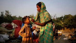 Marjina cleans the nose of her seven year old son Shahid-ul outside their rented shanty on the outskirts of New Delhi, India.