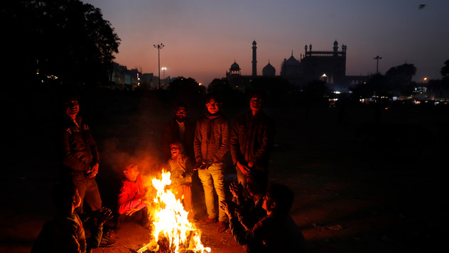 7-year-old Farmaan, fourth from left, and other homeless and daily wage laborers keeps themselves  warm around a bonfire in New Delhi, India.