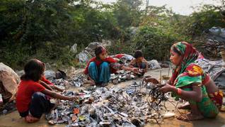 Marjina, right, segregates trash with the help of her children and a young neighbor outside their rented shanty on the outskirts of New Delhi, India, Nov. 11, 2014.