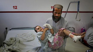 Ismatullah carries his nine-year-old son Eimal, who has lost his right eye and several fingers on his hands in a landmine blast, for bathroom at Emergency Surgical Center for Civilian War Victims in Kabul, Afghanistan, Thursday, Dec. 12, 2019.