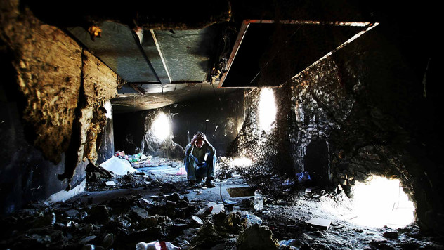 A young Afghan opium addict holds his head as he squats on the dirty floor inside the bombed-out ruins of the former Russian Cultural Center, in Kabul, 2009.