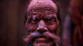 A Hindu devotee, face smeared with colored powder, leaves the Banke Bihari temple during Holi celebrations.