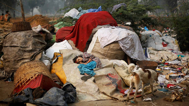 Murshida, 12, lies on a sack of trash after she fell ill, outside their rented shanty, Oct. 2014.