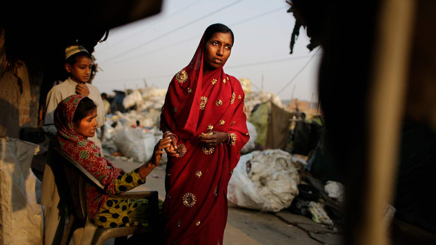 Marjina leaves for the train station after saying goodbye to her neighbors outside her rented shanty on the outskirts of New Delhi, India.