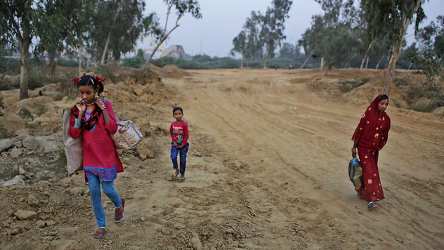 Marjina, right, her daughter Murshida, 12, and seven-year old brother Shahid-ul make their way towards a train station on the outskirts of New Delhi, India.