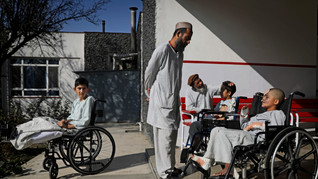 Young Afghan victims of war, Masiullah, left, who lost both his legs in a U.S. airstrike, nine-year-old Eimal, right, who has lost his right eye and several fingers on his hands in a landmine blast, and Ten-year-old Nessar Ahmad, second right, bask in sun outside their ward at Emergency Surgical Center for Civilian War Victims in Kabul, Afghanistan, Dec. 5, 2019.