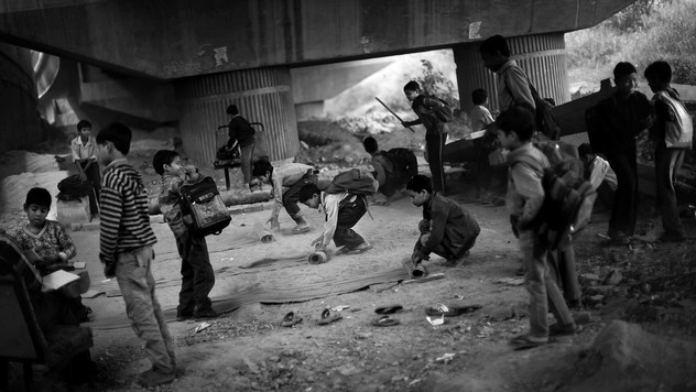 Underprivileged Indian children roll mats to take seats as a class ends at a free school run under a metro bridge in New Delhi, India, Wednesday, Nov. 7, 2012.