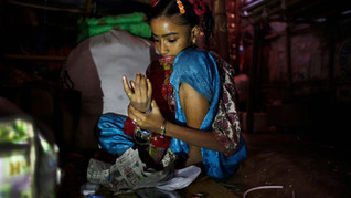 Murshida, 12, puts on bangles as she prepares to leave for a train station, inside her rented shanty on the outskirts of New Delhi, India, Nov. 2014.