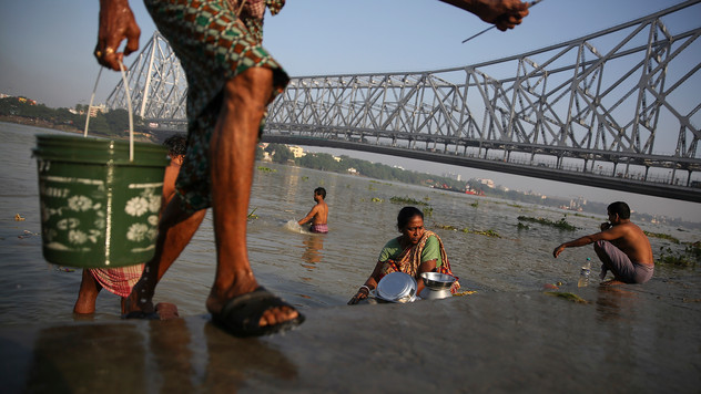 A man carries a bucket of water while people wash utensils, brush their teeth and bathe in the polluted waters of the river Hooghly, a distributary of the river Ganges and known as Ganga by locals, in the backdrop of the landmark Howrah Bridge in Kolkata, in the eastern Indian state of West Bengal, Friday, October 11, 2019. Once the capital of the British raj, today the seething metropolis is home to nearly 15 million people.