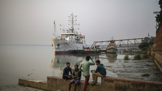 Boys sit by stairs beside a shipyard on the banks of river Hooghly, a distributary of the river Ganges, in Barrackpore, in the eastern Indian state of West Bengal, Thursday, Jan. 16, 2020.
