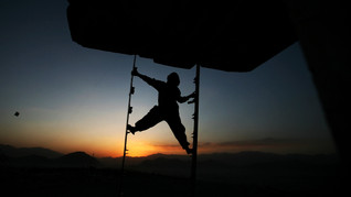 An Afghan boy is silhouetted as he climbs down from the diving board of an unfinished Soviet-era swimming pool as the sunsets in Kabul, Afghanistan, 2009.