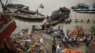 People wait for their turn to cremate a body as piles of logs arrive on boats at Manikarnika Ghat, one of the oldest and most sacred place for Hindus to be cremated, on the banks of river Ganges in Varanasi, India, Friday, Oct. 18, 2019. For millions of Hindus, Varanasi is a place of pilgrimage and anyone who dies in the city or is cremated on its ghats is believed to attain salvation and freed from the cycle of birth and death. Tens of thousands of corpses are cremated in the city each year, leaving half-burnt flesh, dead bodies and ash floating in the Ganges.