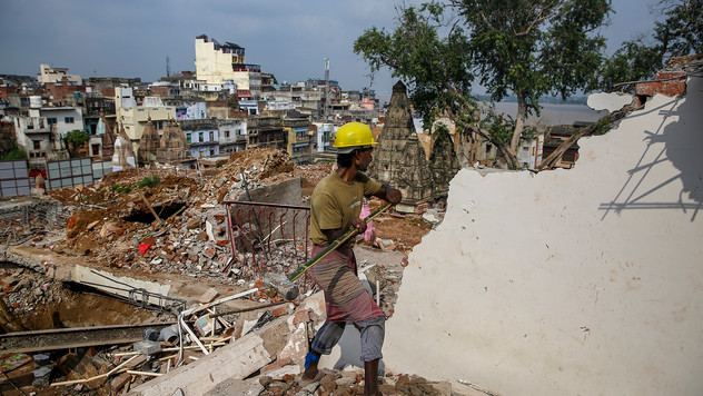 A worker uses sledgehammer to demolish a building at the site of a proposed grand promenade connecting the river Ganges with a centuries-old temple dedicated to Lord Shiva, in Varanasi, one of the Hinduism's holiest cities, in the northern Indian state of Uttar Pradesh, India, Monday, September 23, 2019.