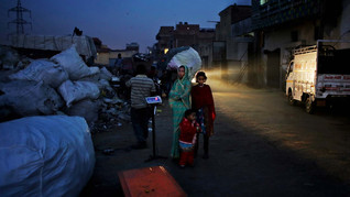 Marjina and her 12-year old daughter Murshida wait for a trash dealer to weigh their segregated trash on the outskirts of New Delhi, India.