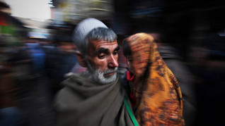 An elderly Afghan man walks as he carries a child boy at a market in Kabul, Afghanistan, 2010.