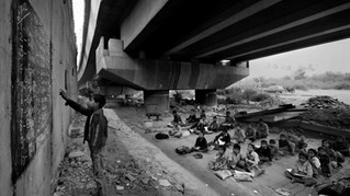 An underprivileged Indian child reads from a black board, painted on a building wall, at a free school run under a metro bridge in New Delhi, India, Wednesday, Nov. 7, 2012.