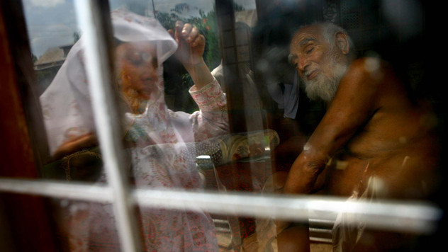 A renowned Kashmiri faith-healer, Ahad Sahab, sits inside his room as a Kashmiri muslim woman is reflected on the glass as she waits for her turn outside the room to see him at Sopore, some 55 kms north of Srinagar, the summer capital of India-administered Kashmir, India, 2007.