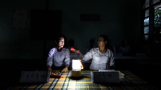 Election officials work inside a poorly lit polling station early morning before starting balloting in Wah Thin Kha, Myanmar, Sunday, April 1, 2012. Myanmar held a landmark election in 2012 which sent democracy icon Aung San Suu Kyi into parliament for her first public office since launching her decades-long struggle against the military-dominated government.