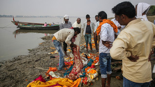 People prepare to cremate the body of a Hindu woman on the banks of the river Ganges on the outskirts of Varanasi, one of the Hinduism's holiest cities, India, Thursday, Oct. 17, 2019. For millions of Hindus, Varanasi is a place of pilgrimage and anyone who dies in the city or is cremated on its ghats is believed to attain salvation and freed from the cycle of birth and death. Tens of thousands of corpses are cremated in the city each year, leaving half-burnt flesh, dead bodies and ash floating in the Ganges.