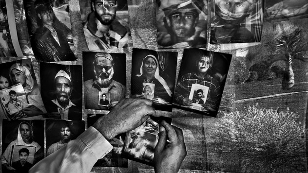 A volunteer puts up photographs of young Kashmiris who have disappeared involuntarily over the years, on the top row, along with photos of Kashmiris holding up portraits of their missing relatives during a demonstration organized by the Association of Parents of Disappeared Persons (APDP) to mark the International Day of the Disappeared in Srinagar, the summer capital of Indian-administered Kashmir, 30 August 2007.